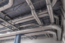 Commercial interior building with ductwork running along ceiling